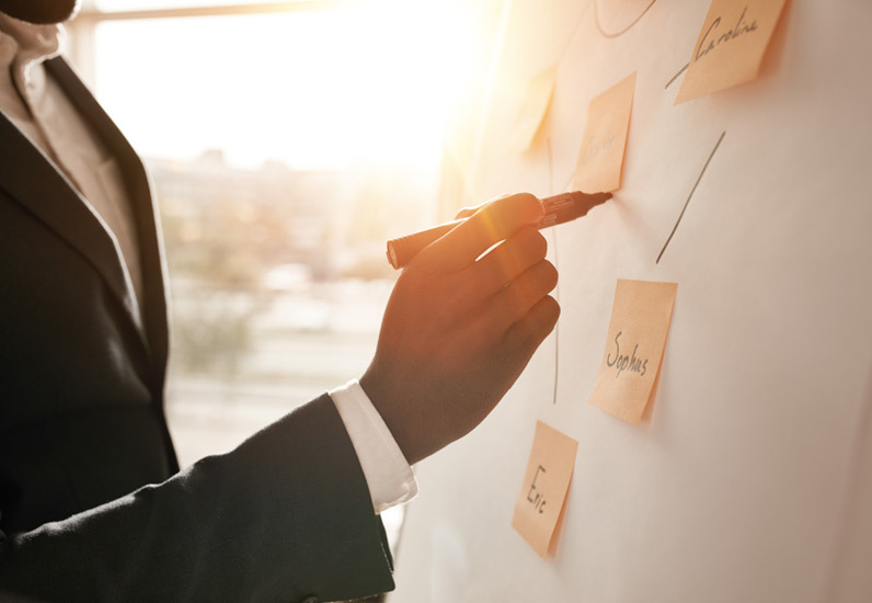 Business professional writes ideas on sticky notes