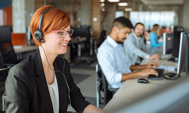 A smiling IT help desk employee wearing headphones sitting alongside her coworkers