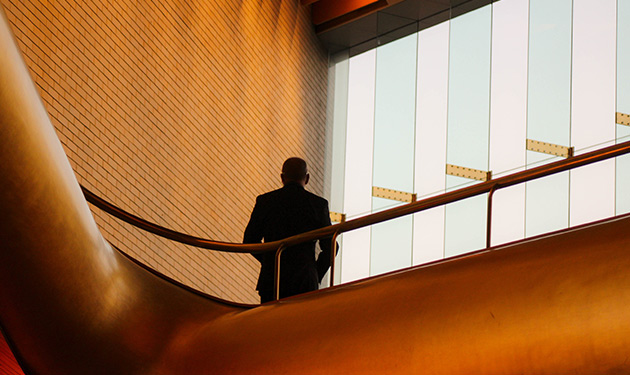 A man stands in a business corridor facing a window