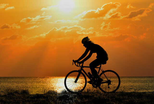 A woman rides her bike in the sunset along side the beach