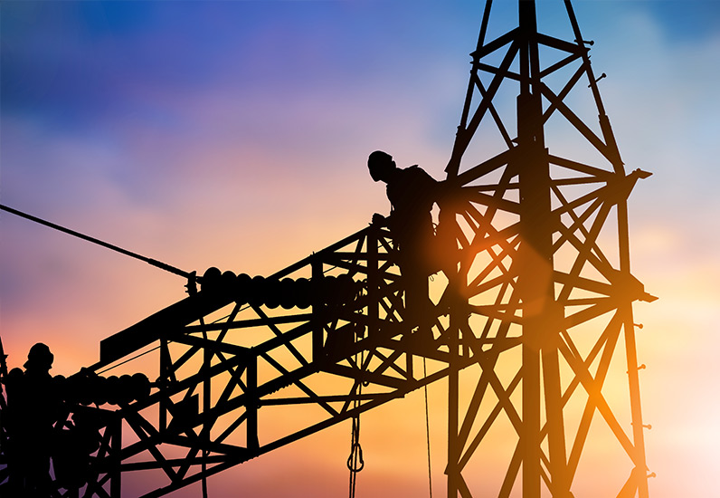 silhouette utility worker on high voltage tower