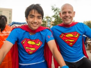 MRE employee posing with superhero cape with teenager at charity event